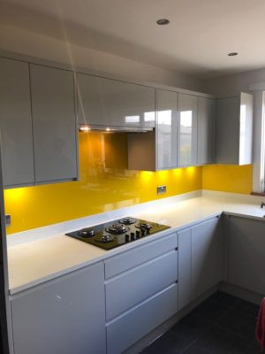 Bright yellow glass splash backs in a domestic kitchen